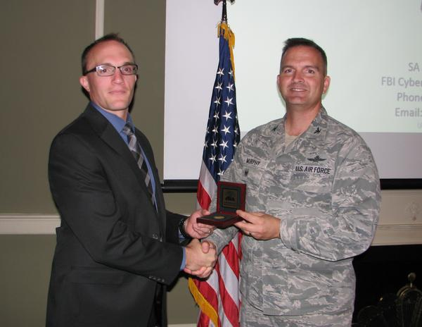 FBI Special Agent Jeremy Witmer, Tech Expo keynote speaker (l), receives a chapter coin from Col. Sean Murphy, USAF, chapter president, at the October event.