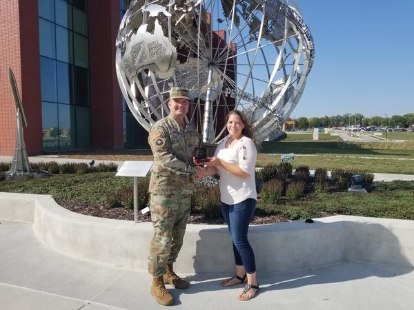 In September, Col. Sean Murphy, USAF, chapter president (l), shakes hands with Jennifer Havenner, chapter vice president of diversity, and presents her with the Distinguished Young AFCEAN Honoree Award for 2019 in front of the new U.S. Strategic Command's Command and Control Facility at Offutt Air Force Base, Nebraska.