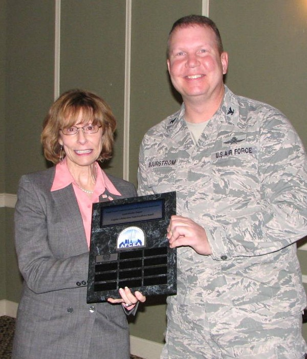 Christy Carpino (l), president, Multi-Option Systems Incorporated (MOSI), shakes hands with Col. Bjurstrom at the October meeting. MOSI is the first chapter program sponsor to receive the distinction of winning the Carpino Collaborative Team Excellence Award.