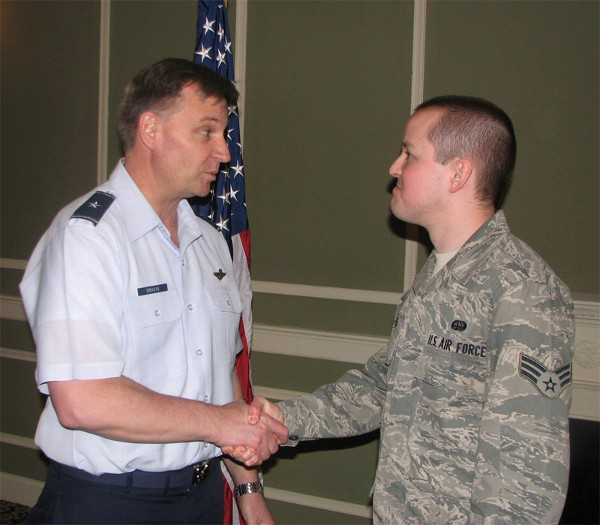 Gen. Dravis (l) shakes hands with Senior Airman Christopher Voss, USAF, lead Young AFCEAN, who received a JTSO coin at the chapter�s March luncheon.