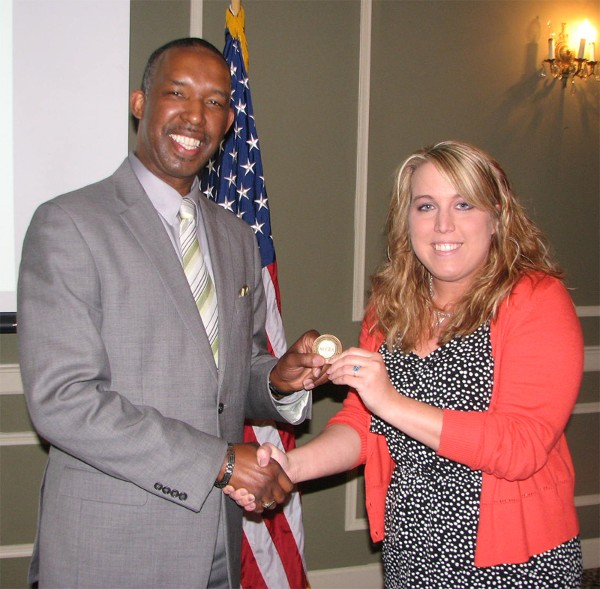 Randy White (l), director, 55th Wing, Equal Opportunity, Offutt Air Force Base, shakes hands with Lexi Eker, chapter assistant diversity liaison. White received a chapter coin for addressing the chapter at the May luncheon on how individual experiences are unique and help formulate perceptions of others.