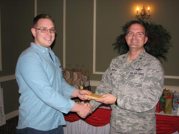 Staff Sgt. Hunter Christiansen, USAF, chapter vice president of membership, receives congratulations from Col. Murphy after receiving the chapter's Meritorious Service award in December for his contributions over the last two years.