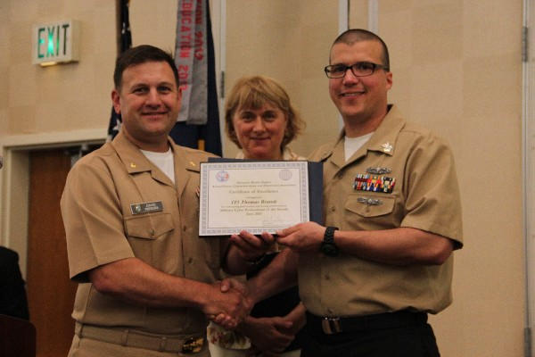 Lt. Cmdr. Dave Pereira, USN, (l) chapter vice-president of military affairs, presents the June Military Cyber Professional of the Month to Petty Officer 1st Class Thomas Brandt, USN, Naval Computer Telecommunications Area Master Station, Atlantic. Teresa Duvall, chapter president, stands witness.