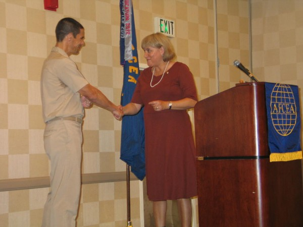 Teresa Duvall, chapter president, extends her gratitude by presenting a chapter coin to Capt. John W. Chandler, USN, commander, Naval Network Warfare Command, as guest speaker at the August monthly luncheon.