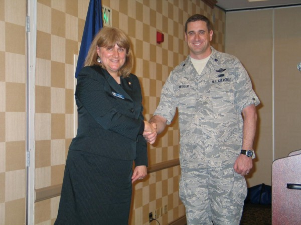 Teresa Duvall, chapter president, extends gratitude to Lt. Col. Michael G. Messer, USAF, is the senior joint fires, maneuvers, and cyberspace analyst at the Joint and Coalition Operational Analysis Directorate, Joint Staff, for his speech at the March luncheon.