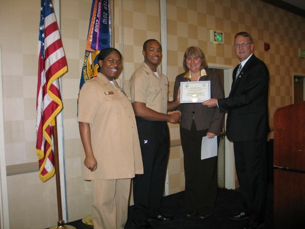 Teresa Duvall (2nd from r), chapter president, presents the chapter's December Military Cyber Professional Award to Petty Officer 3rd Class Frankie Langford, USN (2nd from l), Naval Computer Telecommunications Area Master Station, Atlantic. Senior Chief Petty Officer Latrina D. Tate, USN, and Doug Vanderlip, chapter executive vice president, stand witness.