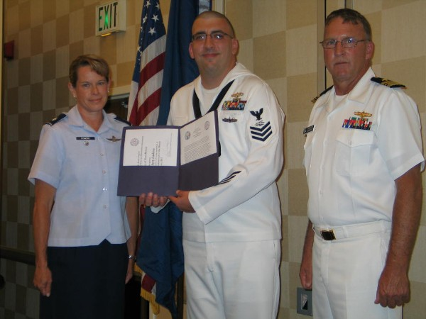 Lt. Cmdr. Doug Vanderlip, USN (l), chapter executive vice president, and Lt. Col. Jenniffer Romero, USAF, chapter Awards Committee, present the July Military Cyber Professional of the Month Award to Petty Officer 1st Class Robert Jenkins, USN, Expeditionary Strike Group Two.