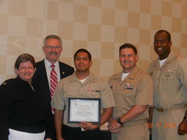 Whit Ludington, chapter president (2nd from l), presents the September Military Cyber Professional Award to Information Systems Technician Seaman Mario Gutierrez, USN (c), as Capt. Barrett (l), Lt. Cmdr. Dave Pereira, USN (2nd from r), chapter vice president for military affairs, and Information Systems Technician Master Chief Jeff Price, USN, stand witness.