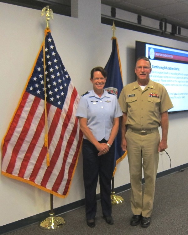 Lt. Col. Jenniffer Romero, USN, chapter vice president for military affairs, and Lt. Cmdr. Doug Vanderlip, USN, chapter president, greet each other at the Cyber Lunch and Learn in May.