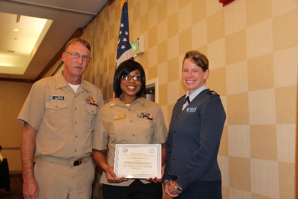 In November, Lt. Cmdr. Doug Vanderlip, USN, chapter president, and Lt. Col. Jenniffer Romero, USAF (r), chapter vice president for military affairs, present Information Technician Systems 1st Class Kwelisha Jackson, USN, with the Military Cyber Professional of the Month Award.