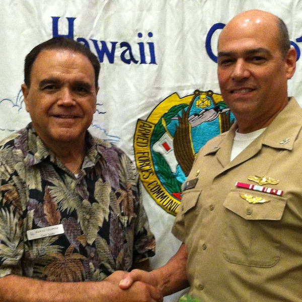 Cory Lindo, chapter president (l), greets January luncheon speaker Capt. William Dodge, USN, commanding officer, Naval Computer and Telecommunications Area Master Station, Pacific.