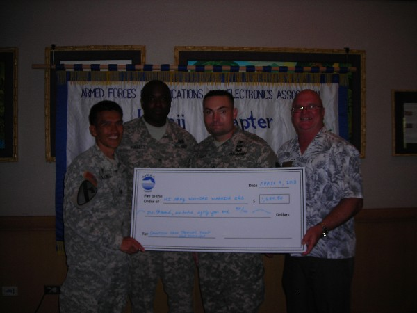 Ed Ryglewicz (r), regional vice president, presents proceeds raised from the chapter's annual golf tournament to representatives of the Hawaii Army Wounded Warrior Organization in April.