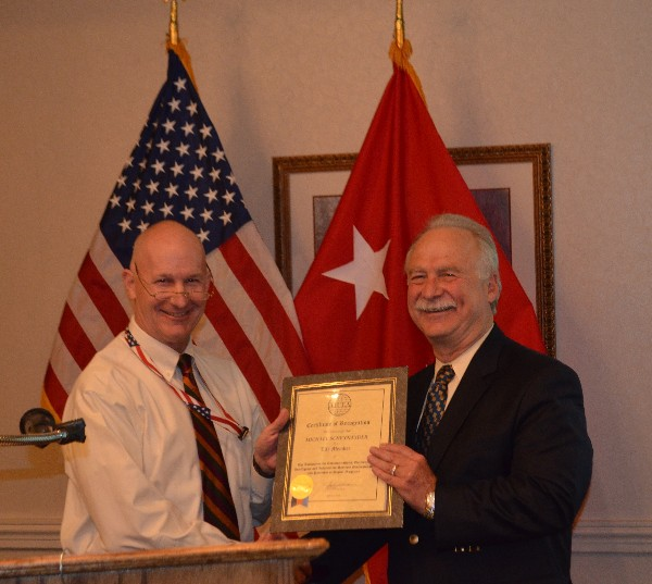Col. Bob Bell, USA (Ret.) (l), presents Schexnayder with an AFCEA lifetime membership award in May.