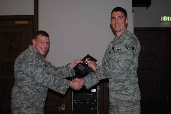 Senior Airman Douglas Clark, USAF (r), receives the Young AFCEAN Emerging Leader of the Month Award from 2nd Lt. Jason Loomis, USAF, during the February luncheon.