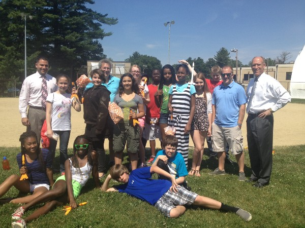 Bud Vazquez, chapter president (far r) joins Matt Deutsch, Young AFCEAN Rocket Box program coordinator (far l), science teacher Fred Lipton (back row, second from l), and Hanscom Middle School students in celebrating Rocket Day in June.