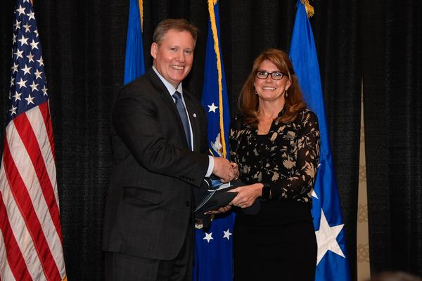 At the chapter's annual State of the Air Force Life Cycle Management Center (AFLCMC) Luncheon in January, Chapter President Pat Dagle (l) presents the AFCEAN of the Quarter Award to Michele Cimino, Booz Allen Hamilton, for her volunteerism and go-getter spirit.