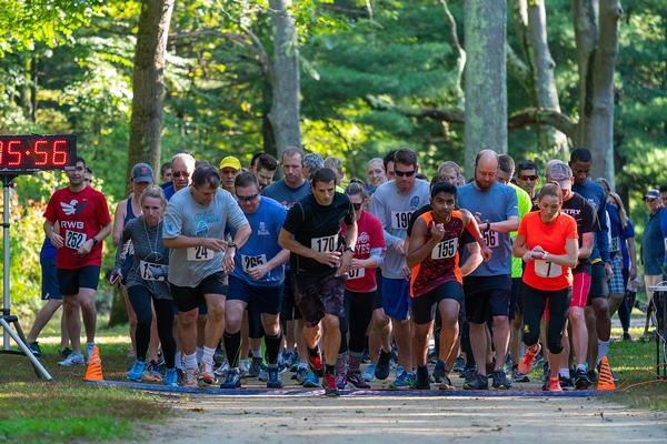 Men's winner Mike Dimauro, wearing bib No. 170 (c), and women's winner Lindsay Willard, wearing bib No.7 (far right), start their race toward victory at September's Young AFCEAN 5K Run for STEM.