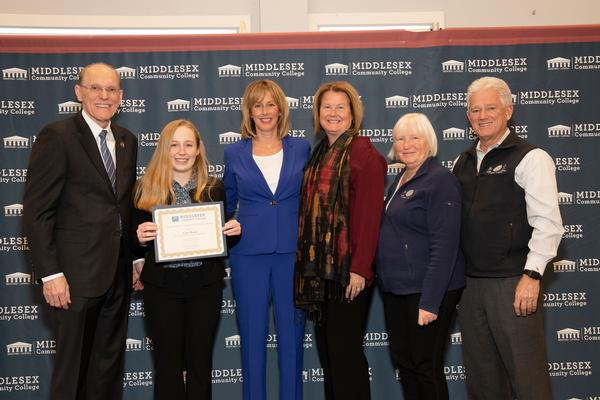 Ceara Herget, recipient of the chapter's $2,000 Thomas P. O'Mahony Spirit of Excellence STEM Scholarship (2nd from l) receives certificate and congratulations in March from (l-r) Jim Mabry, president of Middlesex Community College; Lorrie Christo and Jeannine Robbins-Murphy, O'Mahony's daughters; Claire Goulet, chapter vice president, operations; and Chris Hitchcock, director and treasurer of Middlesex Community College Foundation.