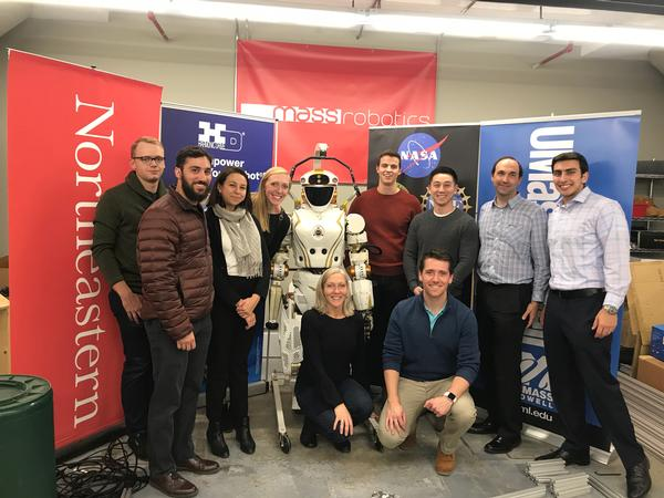 In November, Joyce Sidopoulos, co-founder of MassRobotics (front l), and Will Keller, YAC industry vice president (front r), are pictured with a group of chapter YACs in front of the NASA Valkyrie robot—just one of many robots that startups in the MassRobotics shared workspace may use to test out their innovations.