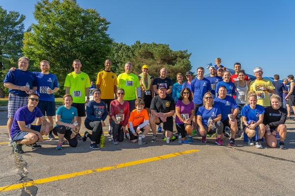 A group of race participants gathers for a photo at the September STEM fundraiser run that included people of all ages.