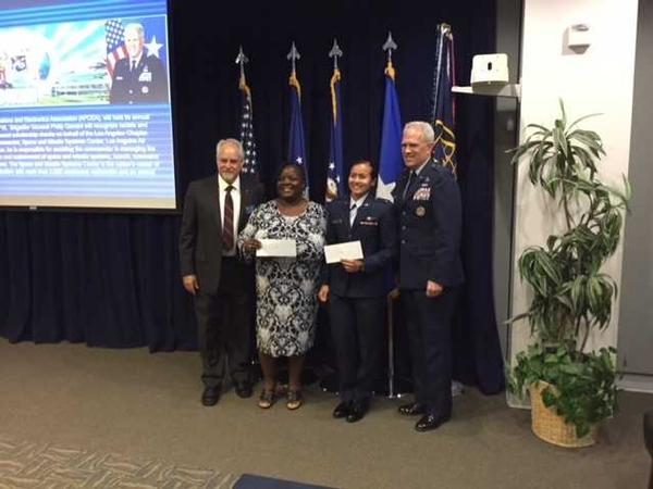 Douglas Holker, AFCEA regional vice president (l), and Brig. Gen. Philip Garrant, USAF, vice commander, Space and Missile Systems Center, Los Angeles Air Force Base (r), present scholarships at the chapter's September awards luncheon to Gloria Dees (2nd from l) and 2nd Lt. Alejandara Mejia, USAF. Recipient 2nd Lt. Marcy Gouri, USAF, was not present.