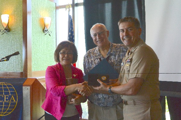 Cmdr. Martin Sabel, USN (r), chapter president, presents Rick Markle, chapter treasurer, and his wife Sadako with a farewell certificate and traditional Latte Stone replica in September.