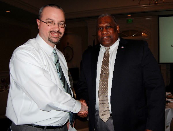 Herbert Hunter (r), director, Business Enterprise Division, Business and Enterprise Systems Directorate, Maxwell Air Force Base-Gunter Annex, shakes hands and networks with a luncheon attendee following his presentation in February.