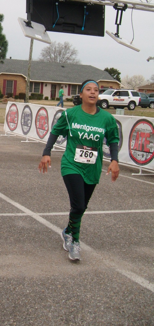 Capt. Ethel Seabrook-Hennessey, USAF, crosses the finish line after running in the Centerpoint Half-Marathon with Team YAAC in March.