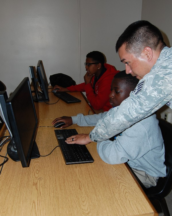 An airman from Gunter Annex volunteers at Camp IT in February, assisting a student during a hackathon session.