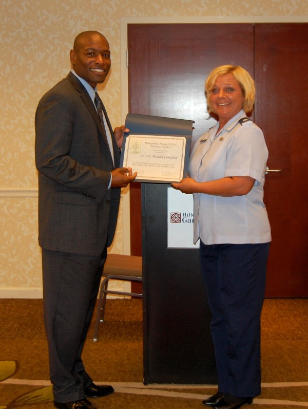 Col. Crawford accepts a certificate of appreciation from Eric Sloan, president of the Montgomery Young AFCEA Chapter, in August.