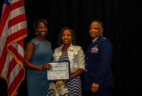 In May, Dena Moncrief (c) accepts a $2,500 Robotics donation on behalf of Floyd Middle Magnet School's Technology Student Association from Stokes (l) and Lt. Col. Boothe.