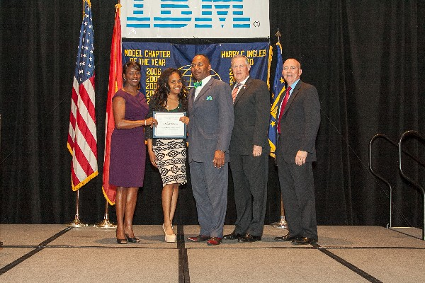 Alabama State University senior Chelsea Roberson (2nd from l), with dad Nate Roberson (c), receives an Education for Industry scholarship from Stokes (l), alongside Gen. Shea (2nd from r) and Shofner, during the annual awards luncheon in May.