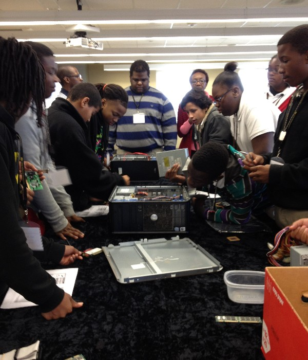 Students disassemble a computer during a hands-on PC assembly workshop at Camp IT in February.