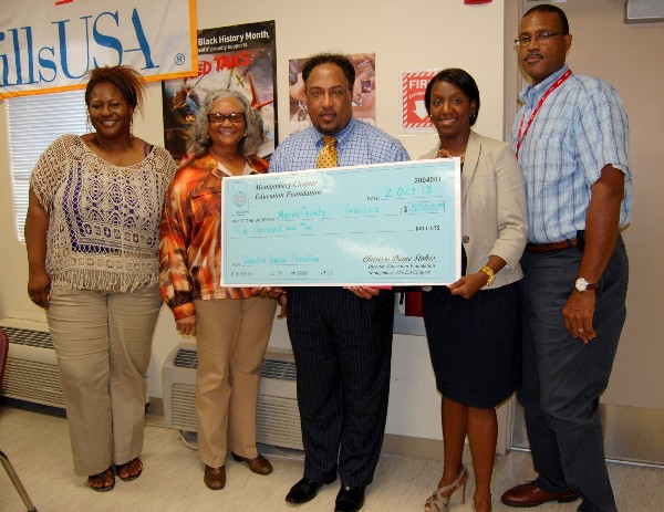 Dr. Melvin Lowe (c) is joined by three Macon County Career and Technical Education Center instructors in October while accepting a robotics donation from Stokes (2nd from r).