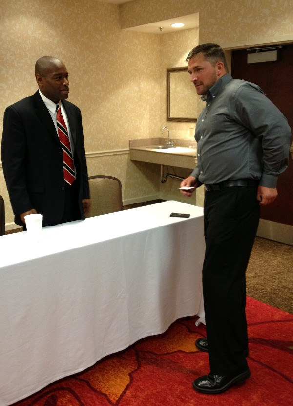 Sloan (l) networks with an attendee at the May Business Over Breakfast event.