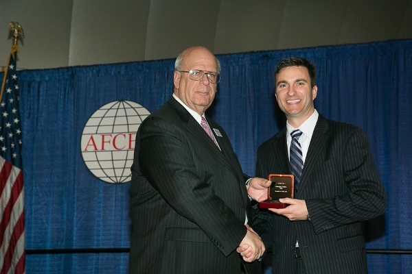 Ryan Cox (r), Oracle, receives the Emerging Leadership Award from Kent R. Schneider, president and chief executive officer, AFCEA International, at the WEST event in February.