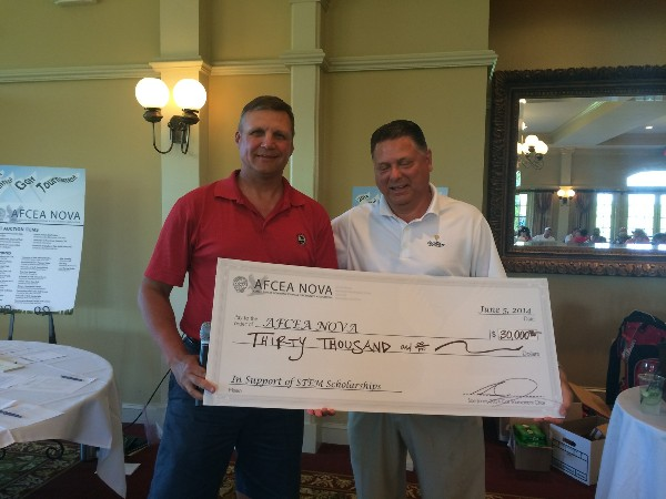 Sam Jones (r), golf tournament chair, presents a check to Ron Zich, chapter president, in June.