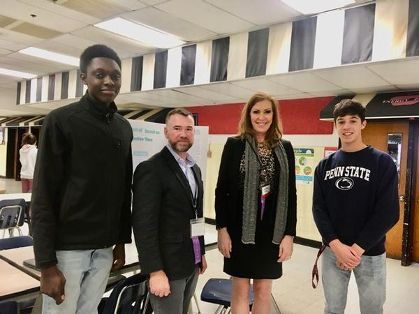 Linda Drake and Rob Landry (c) from the chapter's Education Committee and two students from the Adopt-a-School STEM program at the Herndon High School 2020 Science Fair in January pause for a photo.