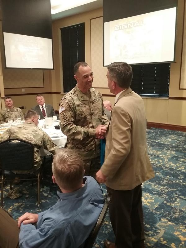Reimers (r) presents Gen. Edmonson a chapter golf shirt and coins as tokens of appreciation for speaking at the June luncheon.