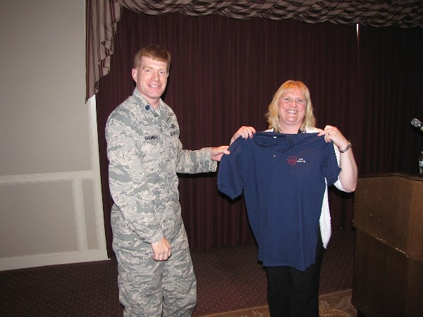 Lt. Col. Arnold Saunders, USAF, chapter president, presents a chapter shirt to the September luncheon speaker, Helen Davis, special projects team lead, Enterprise Services Center.