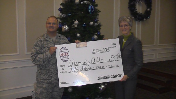 Col. Joseph Sublousky, USAF, chapter president, presents a donation to the Airmen's Attic on behalf of Sarah MacConduibh, vice president of the Air Force Portfolio, MITRE, during the chapter's December luncheon.