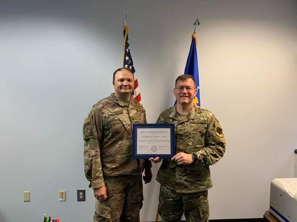 In July, Lt. Col. Richard Sharpe, USAF, chapter vice president (l), presents Col. Richard Brown, USAF, outgoing chapter president, with the AFCEA International Presidential Certification of Appreciation.