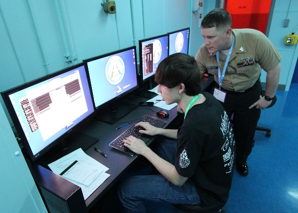 Information Systems Technician 1st Class Kyle Gosser, USN, instructor at the Center for Information Dominance Unit Corry Station, mentors a local high school student participating in the inaugural Cyberthon competition held at the National Flight Academy on board Naval Air Station Pensacola during January. The Cyberthon competition is designed to test student teams on their abilities to use the computer skills they learned in their classrooms to defend and defeat cyber attacks on websites.
