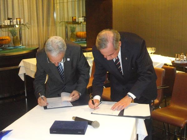 Adm. Durao (l) and Carlos Mineiro Aires, head of the Order of Engineers, sign a protocol at the February dinner.
