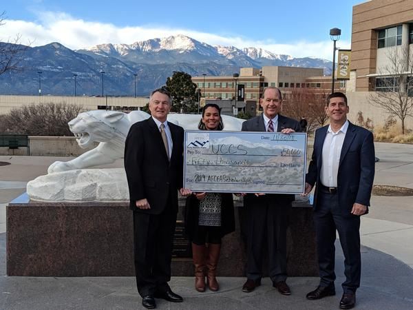 In December, Rod Pohlmann, chair, chapter investment committee (l), and Russ Fellers, chapter vice president for education (far r), present a check for $50,000 for STEM-related scholarships to Zuleika Johnson and Martin Wood, both of the University of Colorado Colorado Springs.