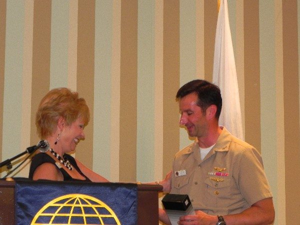 Rear Adm. Christian Becker, USN, shakes hands with Shirley Adams, chapter vice president for programs, following the admiral's speech at the July meeting.