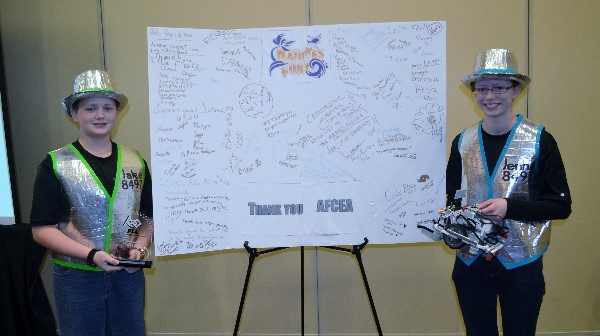 In February, Jake (l) and Jenna Gulick, team leads for the FIRST Lego League (FLL) team Da Ex Bots, display their FLL trophy and winning Lego robot flanking a thank you card to AFCEA from the teams that competed in the rescheduled Southern IL FLL tournament.
