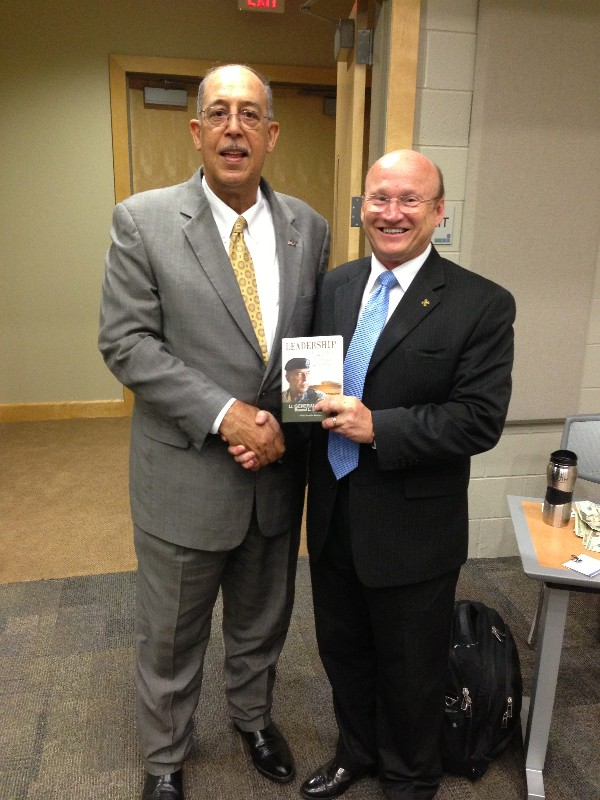 "Lt. Gen. Russel L. Honoré, USA (Ret.) (l), guest speaker at the chapter's April Military IT Day, presents a signed copy of his book ""Leadership in the New Normal"" to Mike Waters, chapter executive vice president."