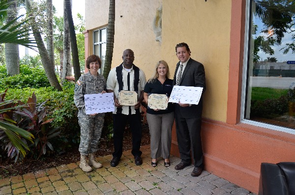 In November, Col. Maria Barrett, USA, chapter president, and Bill Lawless (r), chapter scholarships chairman, present two science, technology, engineering and mathematics grants to Carissa Brazeal, Hollywood Academy of Arts and Science, and Manuel Cox, American High School.