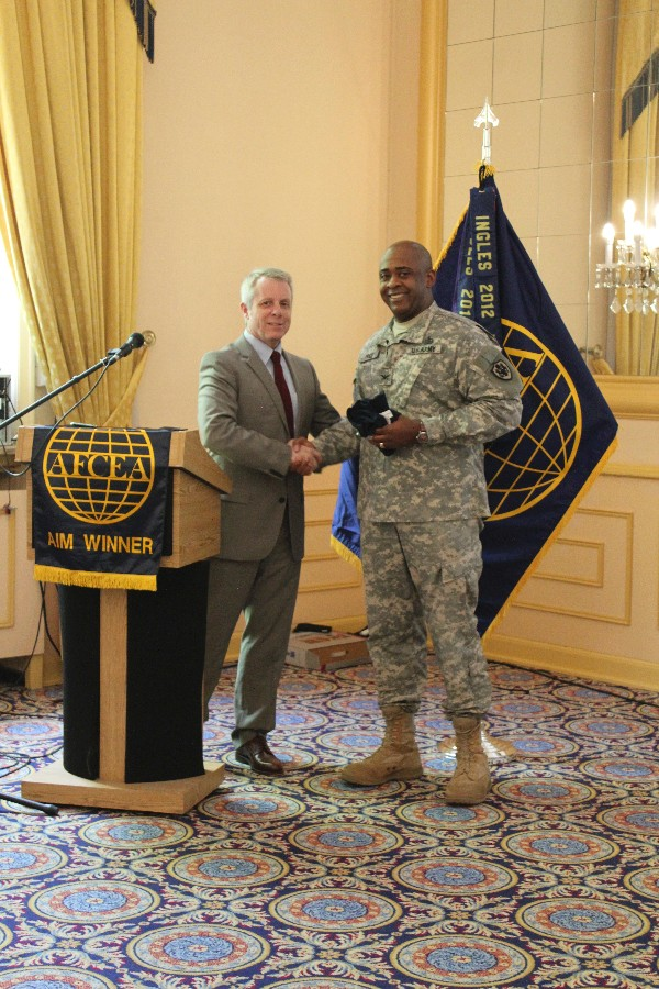 Roger Carpenter, chapter president presents Col. Richard Price, USA, commander of the Defense Information Systems Agency-Europe, with a chapter coin, shirt and plaque as tokens of appreciation for speaking at the June luncheon.
